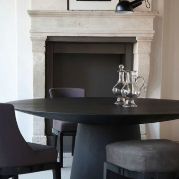 antyczny kominek z nowoczesnym czarnym stołem i tapicerowanymi krzesłami